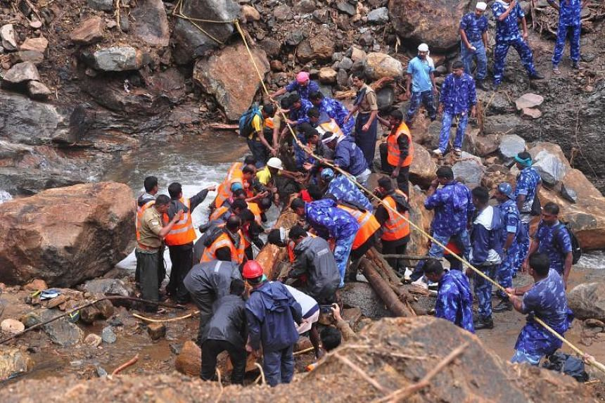 Indian Army personnel and Kerala state police work to build a temporary bridge over a rocky river following heavy flooding in Nelliyampathy in Palakkad district, Kerala, on Aug 20, 2018.