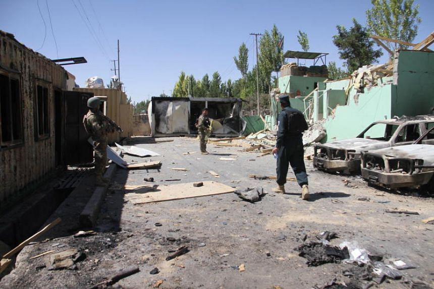 Afghan security forces stand guard at a damaged police station after days of armed clashed between Taleban militants and Afghan security forces in Ghazni, Afghanistan, on Aug 15, 2018.
