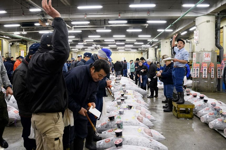 A buyer gestures as he place a bid during the first auction of the year at Tsukiji Market in Tokyo, Japan, on Jan 5, 2018.