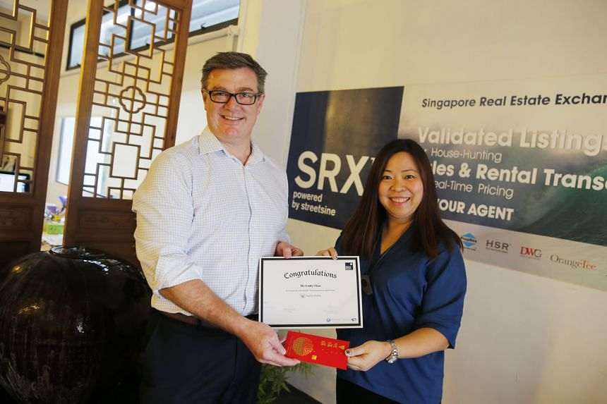 Home owner Emily Chua receiving a certificate and a cash prize of $888 yesterday from Mr Jason Barakat-Brown, chief executive of StreetSine Technology Group, which owns the SRX Property portal that offers the mySG Home service.