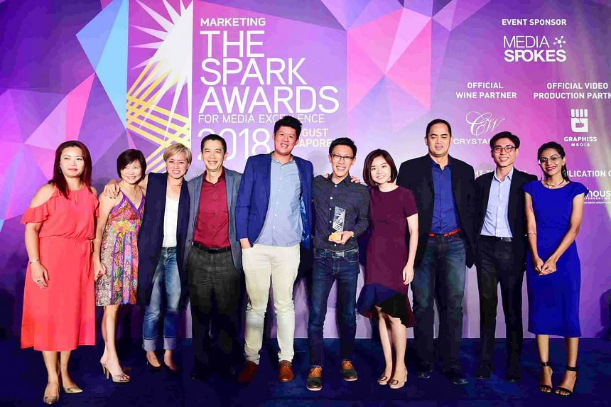 SPHMBO team members (from left) Jesslyn Lock, Julie Wee, Goh Wee Wang, Edward Tang, Denzel Woo, Ian Tan, Clara Cheong, Ken Tay and Caden Cai with a presenter at the Spark Awards for Media Excellence.