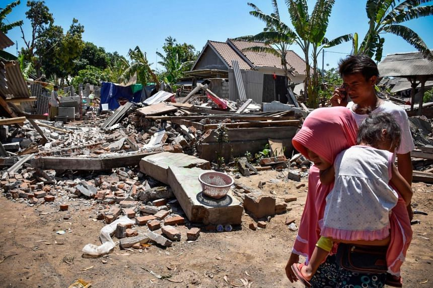 A woman carries her child as they make their way past collapsed homes in the village of Sugar on Indonesia's Lombok island, on Aug 20, 2018, after a series of earthquakes were recorded by seismologists