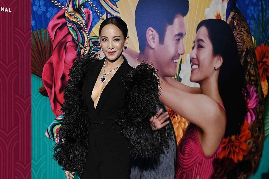 Home-grown actress Fiona Xie (above, on the red carpet of the movie premiere in Singapore on Tuesday) plays a gold-digging bombshell in Crazy Rich Asians. The film is directed by Jon M. Chu (far right, with his wife, graphic designer Kristin Hodge).