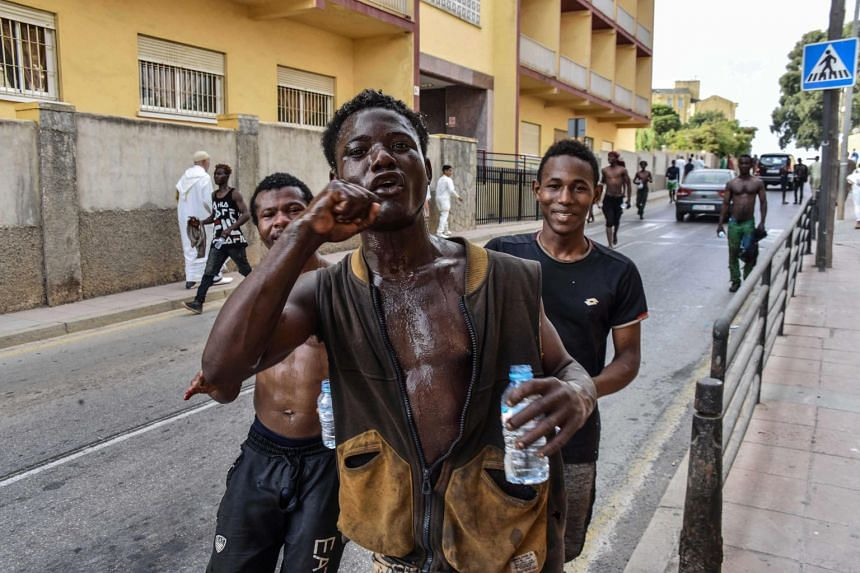 Three men celebrate after over 100 migrants forced their way into the Spanish territory of Ceuta on Aug 22, 2018.