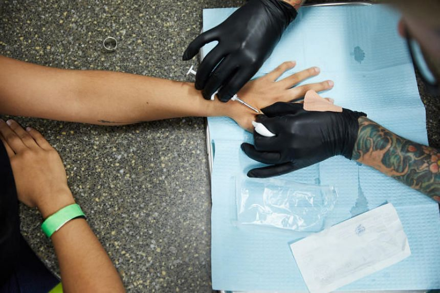 """A woman gets a microchip embedded under her skin during a """"chip party"""" at Three Square Market in River Falls, Wisconsin, in August 2017."""