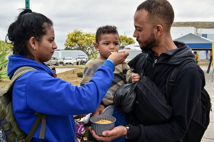 A Venezuelan migrant couple feeding their child as they wait at the binational border attention centre in Huaquillas, Southern Ecuador in the border with Peru, on Aug 24, 2018.