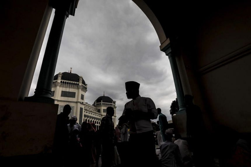 Muslims walk out of a mosque after attending the Eiduladha prayers in Medan, Indonesia, on Aug 22, 2018.