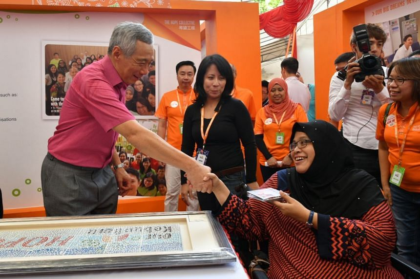 Prime Minister Lee Hsien Loong receiving a mosaic tile from resident Izam Zamah, 48, a beneficiary of a programme run by The Hope Collective group, at Kebun Baru Community Club, on Aug 26, 2018.