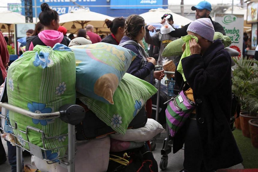Venezuelan migrants arrive at a bus terminal after traveling for 20 hours from Tumbes, northwestern Peru, on Aug 26, 2018.