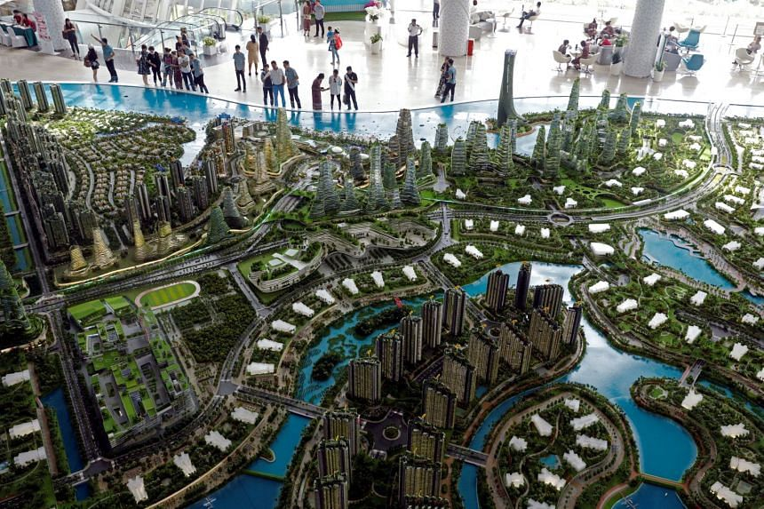 Prospective buyers looking at a model of the development at Country Gardens' Forest City showroom in Johor Bahru, Malaysia, on Feb 21, 2017.