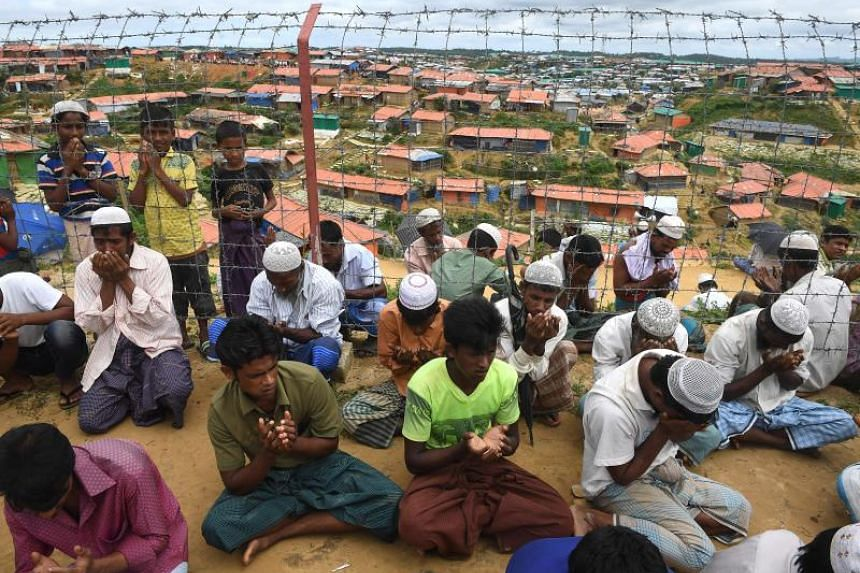 Rohingya refugees perform prayers as they attend a ceremony organised to remember the first anniversary of a military crackdown that prompted a massive exodus of people from Myanmar to Bangladesh, at the Kutupalong refugee camp in Ukhia, on Aug 25, 2