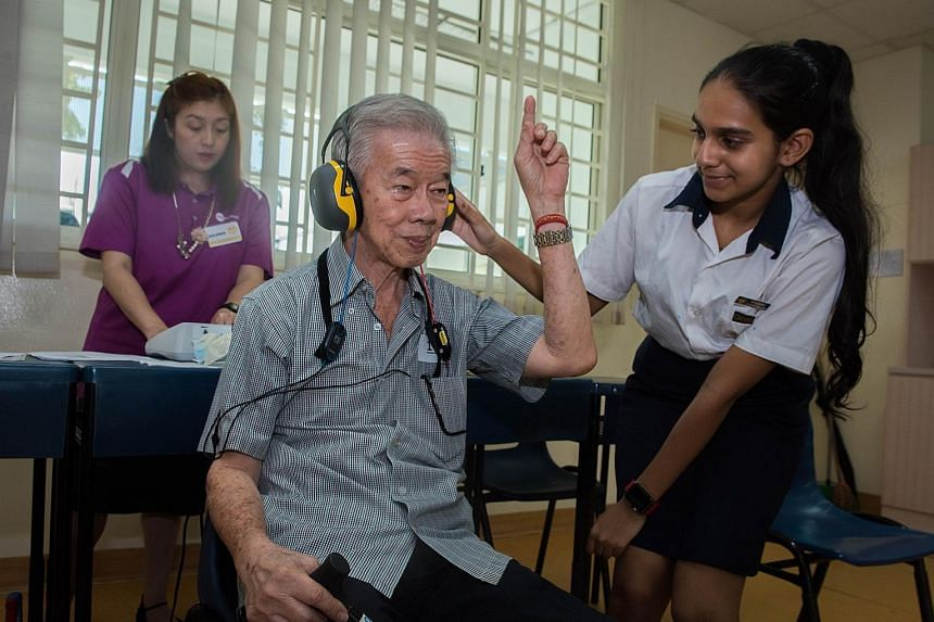 Secondary 2 student Raksha Narayan Rao helping Mr Koh Tiong San, 74, during his hearing check, which was conducted by Ms Mildred Tan (in purple) from a healthcare provider.