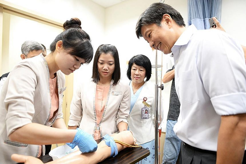 NTUC secretary-general Ng Chee Meng observing TTSH senior patient service associates Woon Shi Mei and Toh Bee Lay demonstrate how to draw blood under the watchful eyes of senior nurse manager Ho Kim Hong.