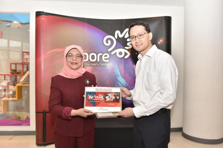 Chairman of Singapore Discovery Centre Adrian Chua presents a framed group photo to President Halimah Yacob during her visit to Singapore Discovery Centre, on Aug 28, 2018.