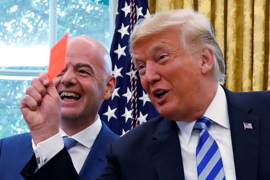 Trump holds up a red card as he meets with Fifa president Gianni Infantino at the White House.