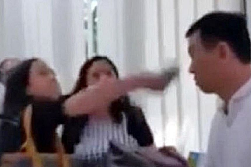 Screengrabs of the video posted online showing (left) one sister splashing a drink at condominium manager Colvin Quek Choon Kiat and (right) the other sister about to hit him. They also caused hurt to security officer Charles Kenneth Bligh.