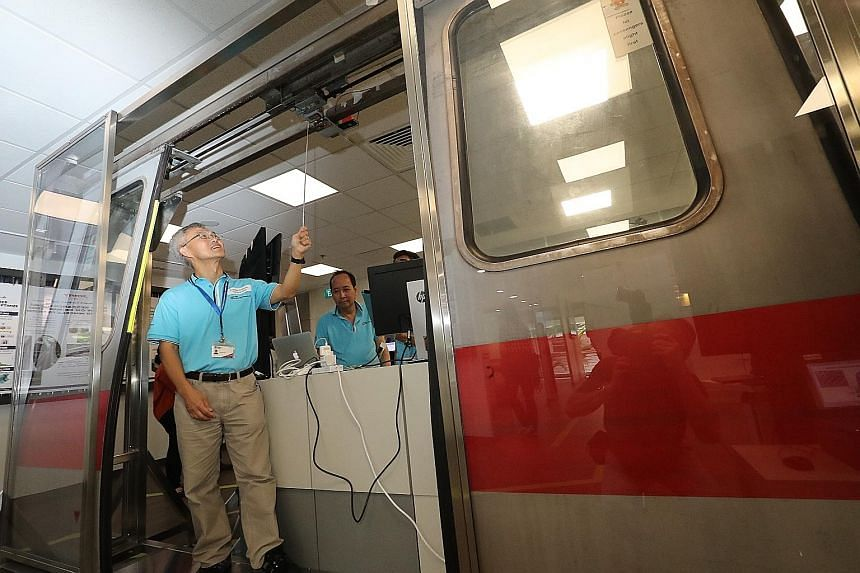 Associate Professor Ling Keck Voon from the Nanyang Technological University pointing to a train door sensor system at the SMRT-NTU Smart Urban Rail Corporate Laboratory.