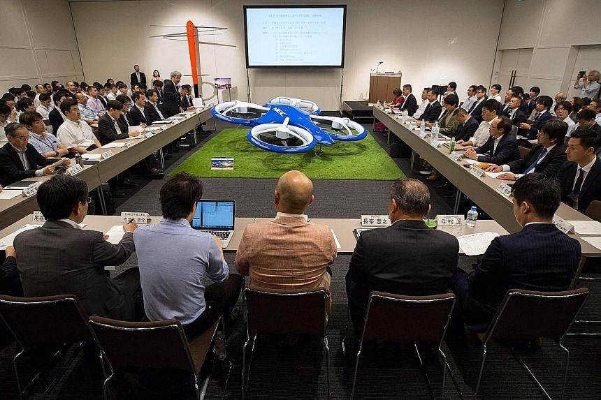 Transportation company executives meeting Japanese officials at the launch of the flying car project yesterday. Japan wants to draw up a road map by the end of the year to commercialise flying cars.