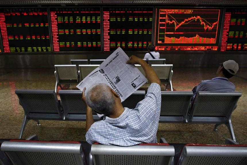 An investor reads a newspaper in front of screens showing stock market movements at a securities company in Beijing, on June 21, 2017.