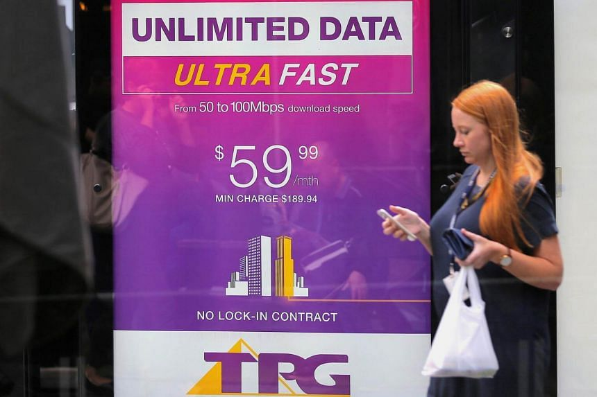A woman looks at her phone as she walks past an advertisement for Australia's TPG Telecom Ltd in central Sydney, Australia, on April 12, 2017.