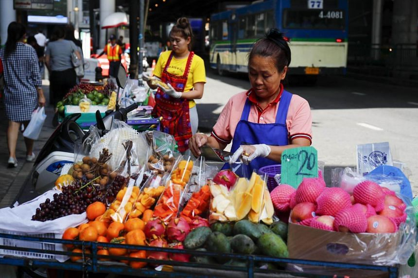 Street fruit vendors ready their stalls on a sidewalk in Bangkok, on Aug 23, 2018.