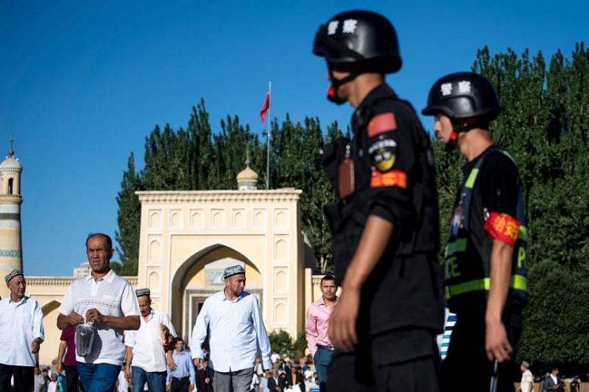 A file photo taken on June 26, 2017, shows police patrolling as Muslims leave the Id Kah Mosque in Kashgar, in China's Xinjiang Uighur Autonomous Region.