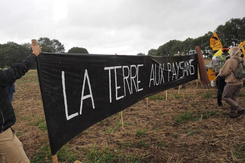 "Members of French farmers union, La Confederation Paysanne, holding a banner that reads ""Land of the people"" as they occupy fields belonging to Chinese farmers during a demonstration in Murs, near Chatillon-sur-Indre, on Aug 29, 2018."