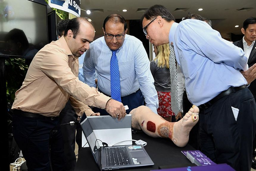 Minister for Communications and Information S. Iswaran (centre) and AI Singapore executive chairman Ho Teck Hua observing a demonstration of artificial intelligence by Dr Hossein Nejati, chief technology officer of health tech start-up KroniKare, whi