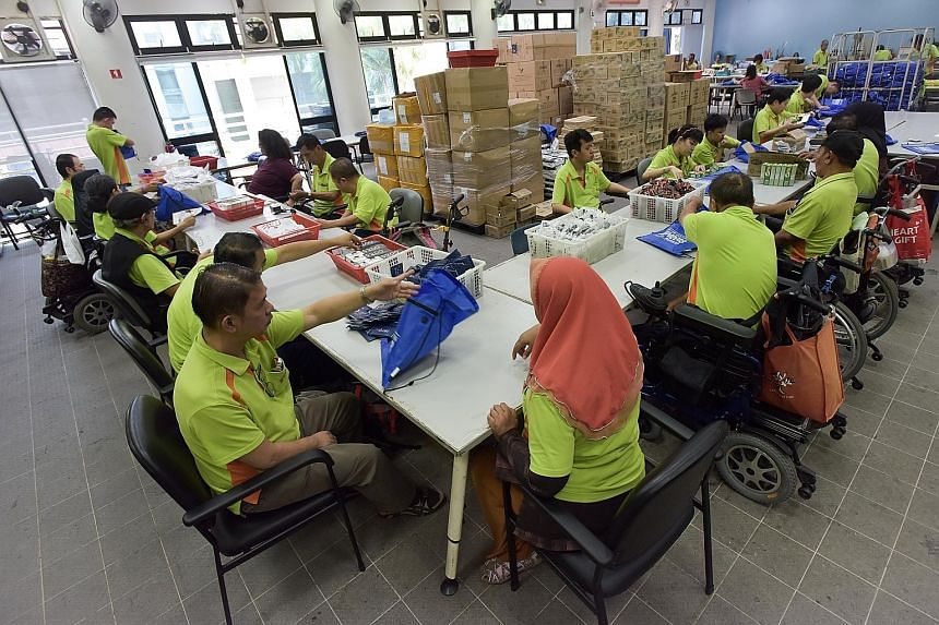 Above: Members of SPD, formerly the Society for the Physically Disabled, filling race packs (left) for participants of the ST Run on Sept 23. The value of the race pack, including items and offers, is over $300.