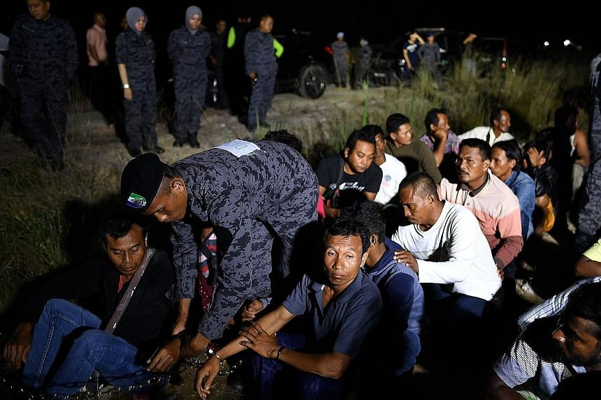 Immigration officers detaining foreigners at a raid last year. Malaysia says it will not extend the amnesty deadline for illegal foreign workers.