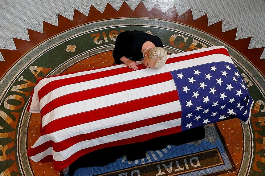 Mrs Cindy McCain, wife of the late US Senator John McCain, kissing his casket during a memorial service at the Arizona Capitol in Phoenix on Wednesday, the first of four days honouring Mr McCain. He will be buried on Sunday at the US Naval Academy in