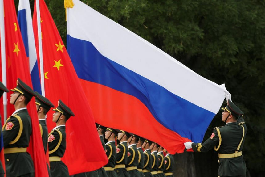 A military officer adjusts a Russian flag ahead of a welcome ceremony hosted by Chinese President Xi Jinping for Russian President Vladimir Putin outside the Great Hall of the People in Beijing on June 8, 2018.