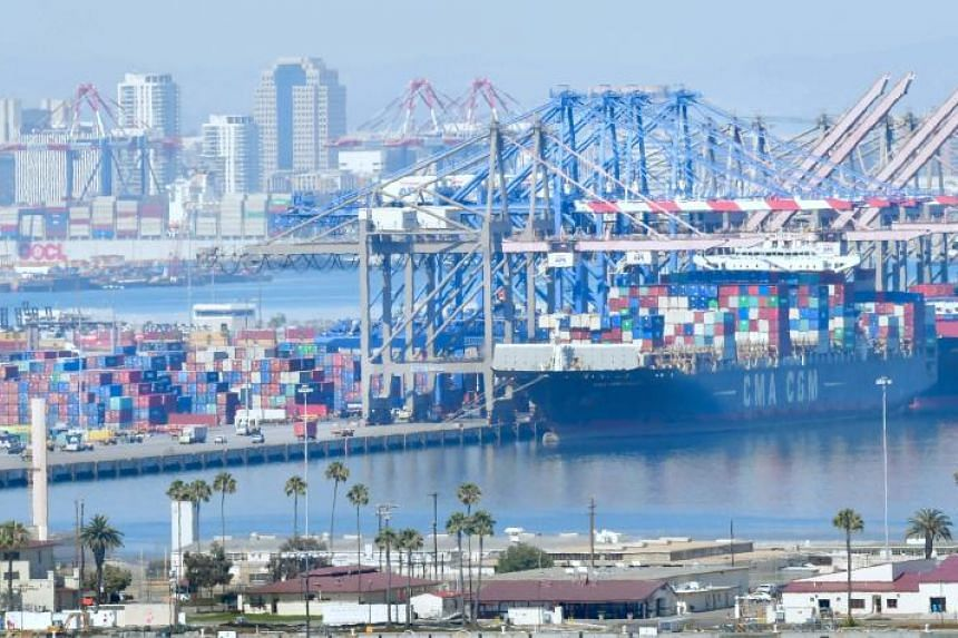 Containers are loaded onto shipping vessels at the Port of Long Beach in Long Beach, California, on July 6, 2018.