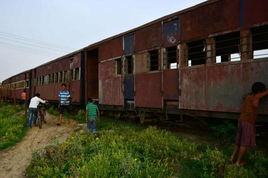 A file photo taken on June 12, 2017, shows children playing near abandoned railway carriages of the Nepal Railway Corporation Ltd in Janakpur.