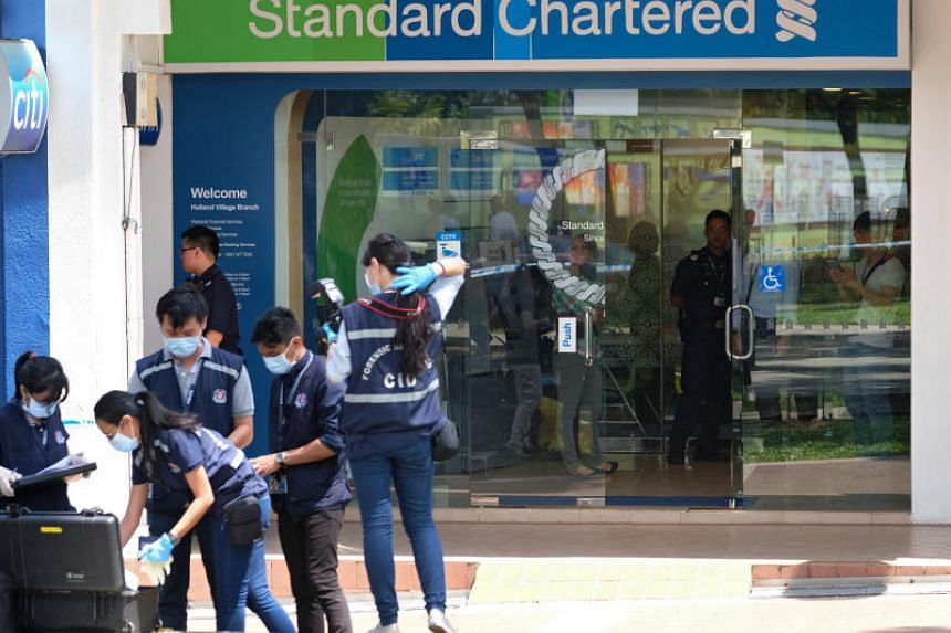 Police officers investigating after a robbery at the Standard Chartered Bank at Holland Village on July 7, 2016.