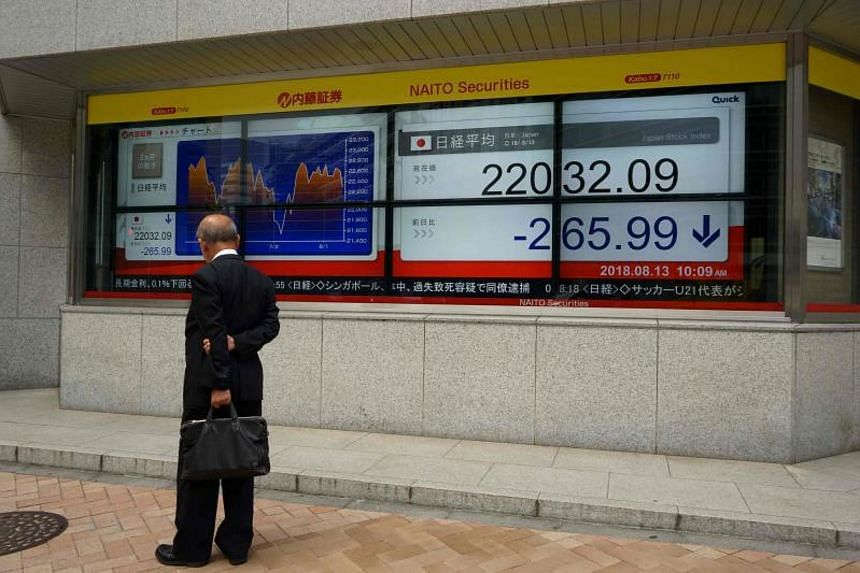 A pedestrian looks at a stock indicator showing share prices of the Tokyo Stock Exchange, on Aug 13, 2018.