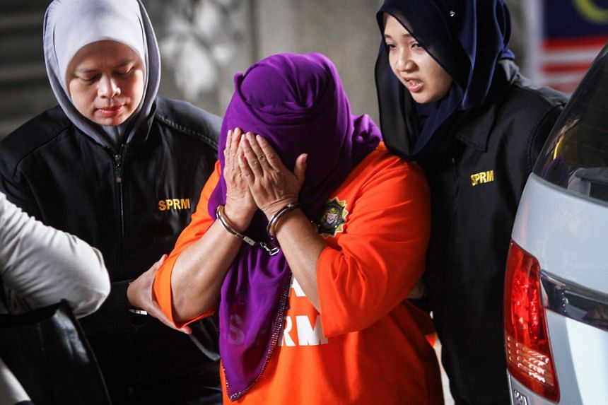 Hasanah Abdul Hamid, former director-general of Malaysia's foreign intelligence agency, is taken to court in handcuffs.