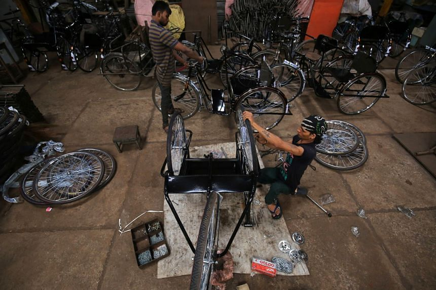 Workers assemble tricycles inside a manufacturing unit in Ahmedabad, India, on Aug 30, 2018.