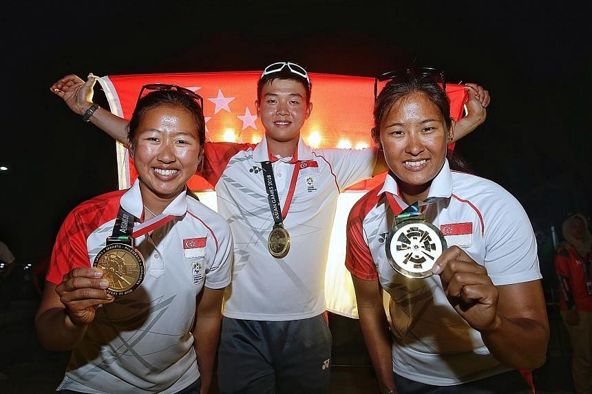 Singapore's 49erFX women's gold medallists Kimberly Lim (left) and Cecilia Low, and Laser Standard bronze medallist Ryan Lo, with their rewards after the end of the sailing competition in Jakarta yesterday.