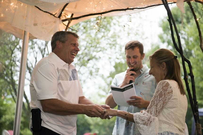 Dave Lindgren puts the wedding ring on Michelle Newman's finger as their son, Martin Schmidt, officiates their wedding in Marshfield, Wisconsin, on Aug 4, 2018.