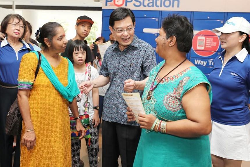 Finance Minister Heng Swee Keat with Madam Sarojah Ayasamy (left), a caregiver, and her sister Madam Paggajam Ayasamy (right) at the Minds Caregivers Wellness Day on Sept 1, 2018.
