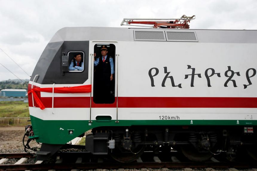 Chinese train masters look out from a train as they wait for passengers during the inauguration of the new train line linking Addis Ababa to the Red Sea state of Djibouti, in Addis Ababa, Ethiopia, on Oct 5, 2016.