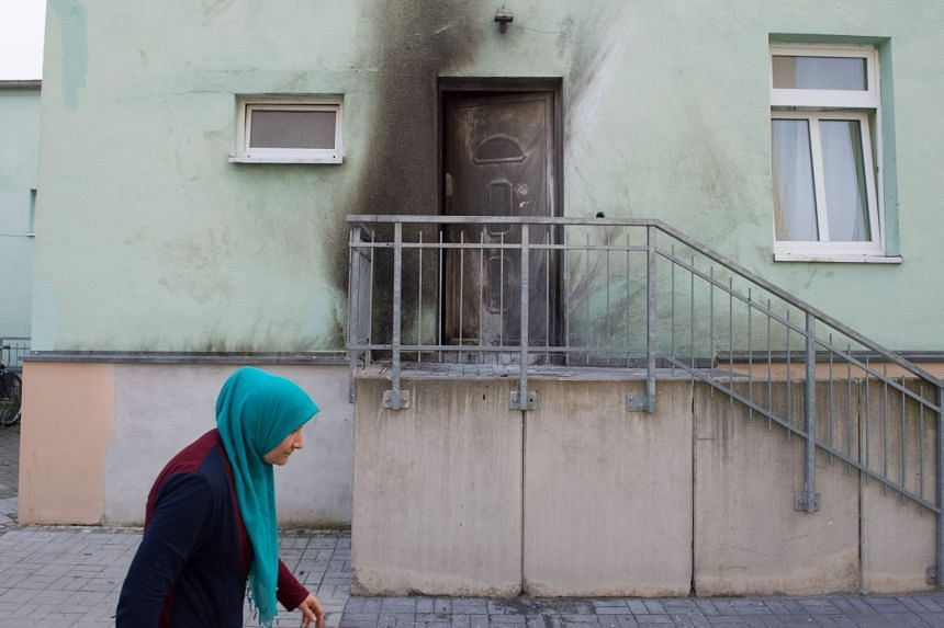 A woman walks past the entrance to the Fatih Camii Mosque in Dresden, eastern Germany, where traces of smoke can be seen after a bomb attack, on Sept 27, 2016.