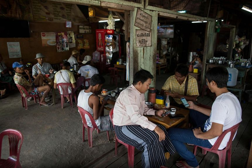 Myanmar people gather for refreshments at a teashop in Yangon, where many hangout to chat and browse Facebook with their mobile phones, on Aug 31, 2018.