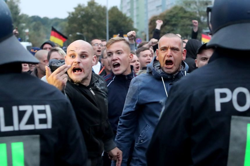 Right-wing protesters shout behind a row of police men in Chemnitz, Germany.