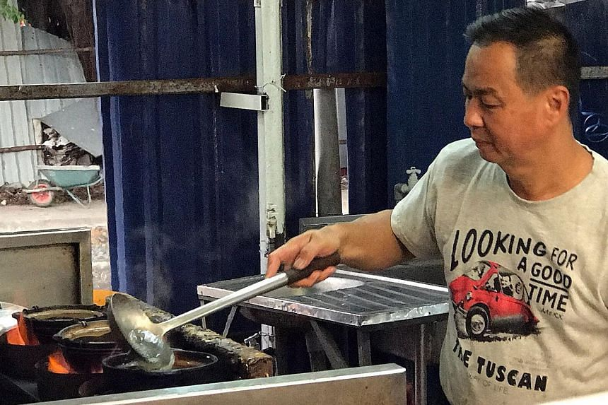 Owner Andy Lye of duck stall De' Champion Ducks (left) roasts between 20 and 25 birds every day to cater to his customers in Petaling Jaya. Mr Yap Seng Eng preparing his signature dish, claypot salted pork porridge, in Petaling Jaya.