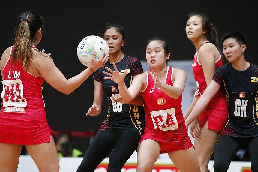 Singapore's goal attack Toh Kai Wei is poised to receive the ball from wing attack Kimberly Lim in the Asian Netball Championship match against Brunei yesterday. Toh contributed 15 goals in the Republic's 68-19 win over the Bruneians.