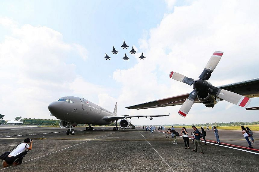(Above): A formation of F-15s soars overhead, while on the tarmac at Tengah Airbase sits the new Airbus A330 Multi-Role Tanker Transport (left). Left: Prime Minister Lee Hsien Loong taking a closer look at the new plane, accompanied by officials.