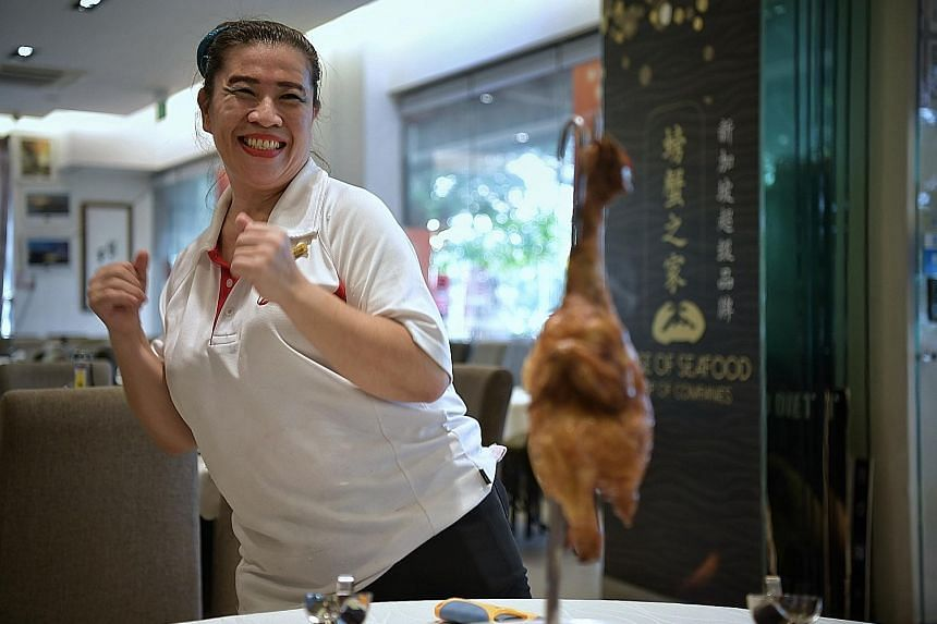 "In the video, Madam Loh Feng Ling dances while, step by step, explaining the $38 flambe chicken dish she is serving. She ends her presentation with a shake and shimmy and the line in Mandarin: ""I hope I have gained your satisfaction."""