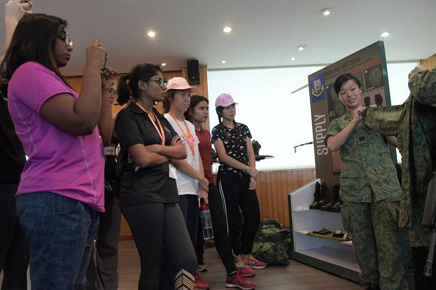 Captain Tracy Thng showing participants how to fold up the sleeves of the army camouflage uniform.